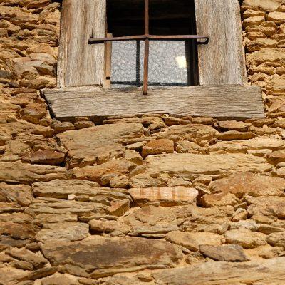 Ventana en fachada de piedra de Sierra Norte